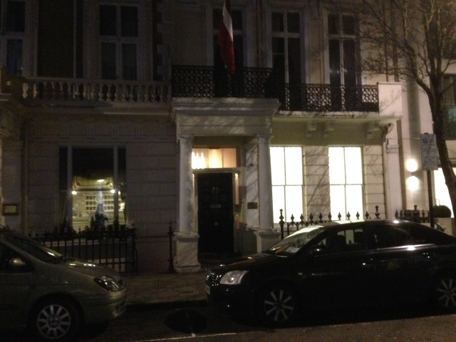 I'm going to go out on a limb and say that hanging above the door is the Latvian flag.